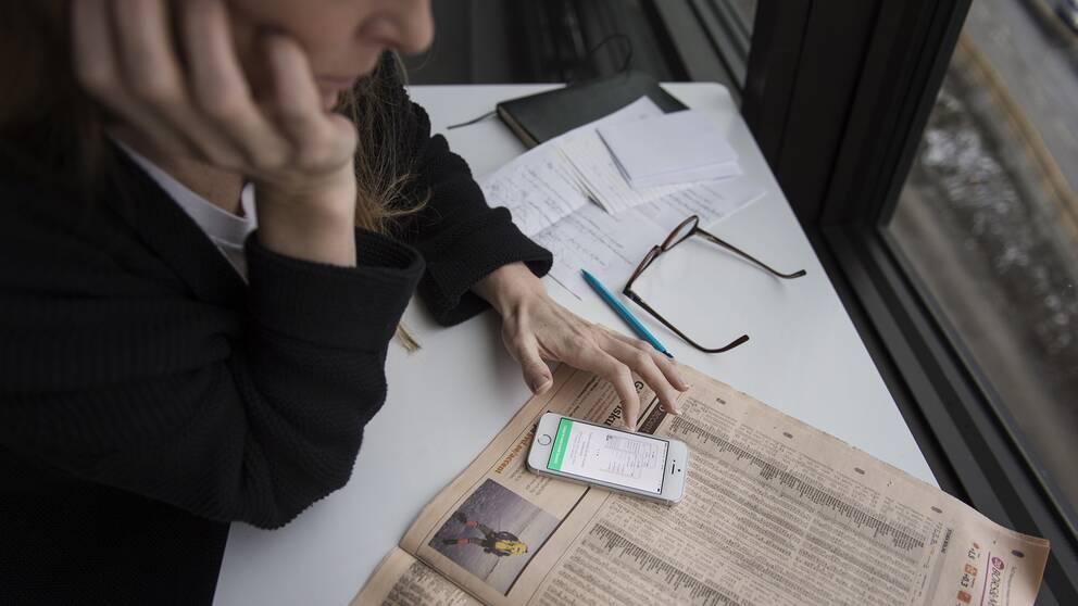 Kvinna som sitter med en tidning och en app.