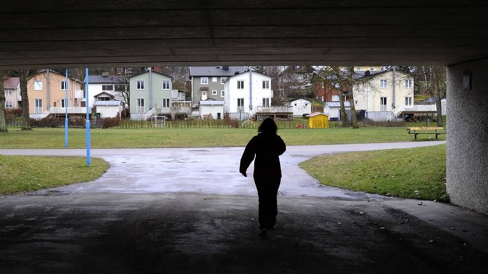 Bild på en kvinna som promenerar i en tunnel.