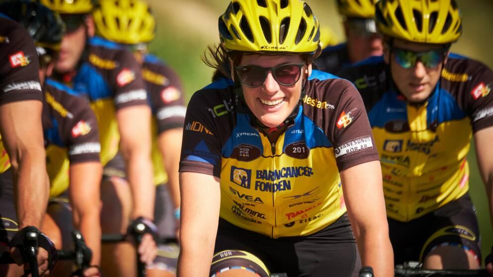 En bild på Johanna Stigmar som cyklar, med fler cyklister i bakgrunden.