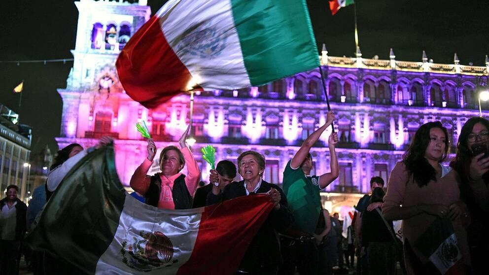 Folksamling som viftar med flaggor