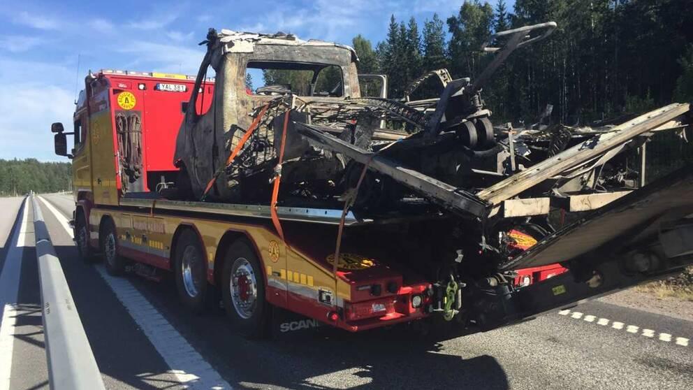 Ett fordon som blivit utbränt bärgas från platsen.