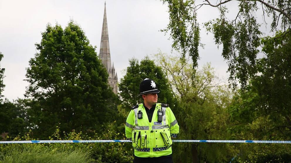 Polisman står och vaktar framför en avspärrning.