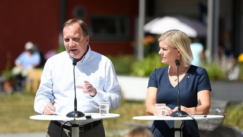 Stefan Löfven och Magdalena Andersson står vid ett bord och talar.