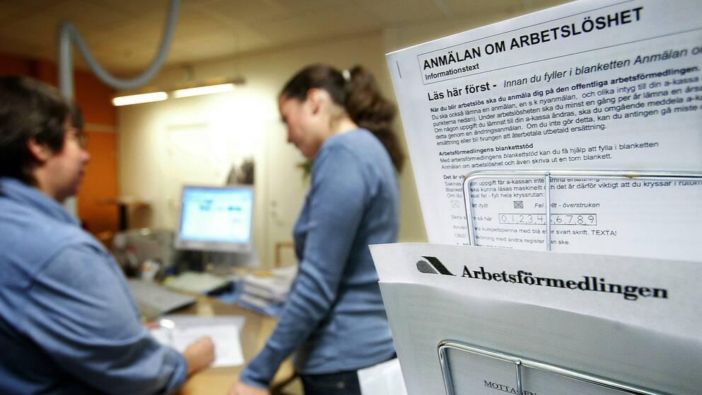 Bild på en handläggare som hjälper en arbetssökande med att fylla i en blankett om arbetslöshet.
