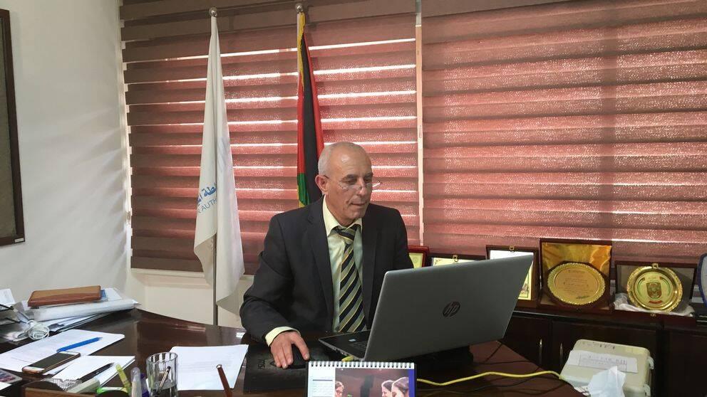Bild på Rehby El Sheikh biträdande chef på Vattenverket i Gaza, som sitter på sitt kontor framför sin dator.