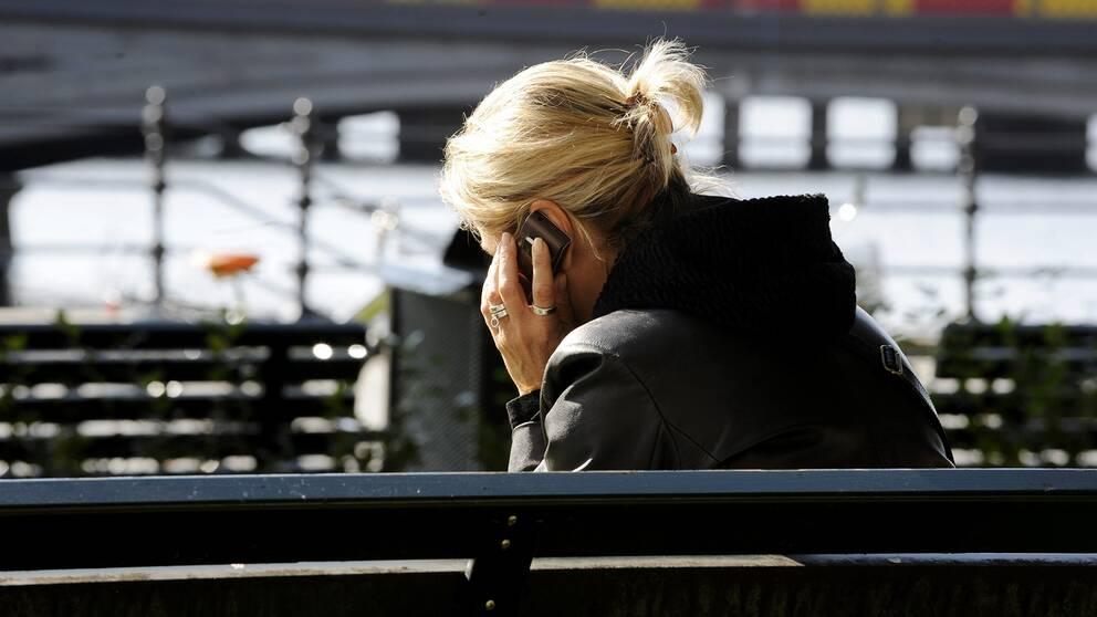 En kvinna sitter på en bänk och pratar i telefon.