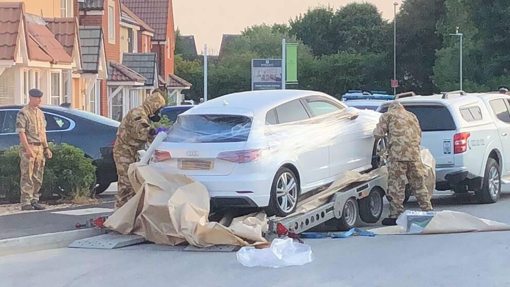 Skyddsklädd polis plastar in den beslagtagna bilen innan de bogserar den därifrån.