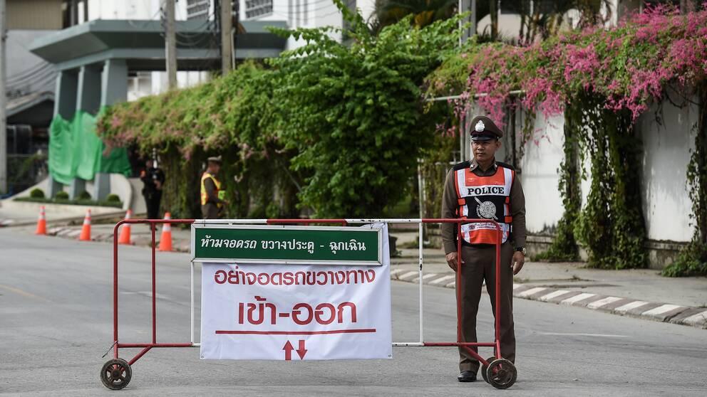 En polis vaktar utanför sjukhuset i Chiang Rai där pojkfotbollslaget nu hålls isolerade efter att ha räddats ur grottan.