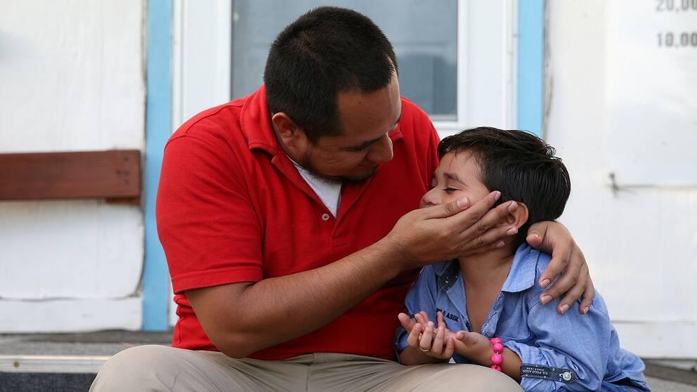 Bild på en sittande man i röd tröja som håller om sin son med en hand på hans axel och en hand på hans kind.