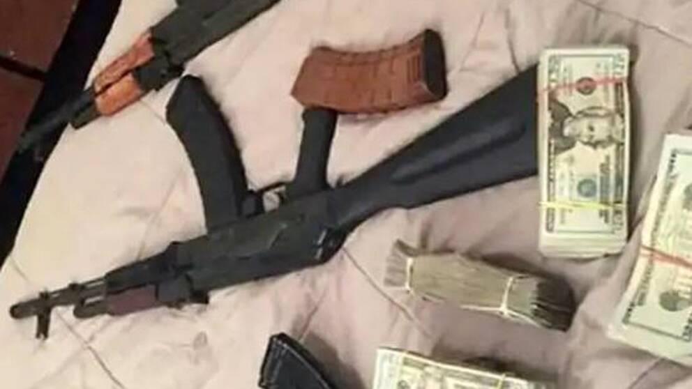 En bild från polisens förundersökning på pengar och skjutvapen på vad som ser ut att vara ett sängöverkast.