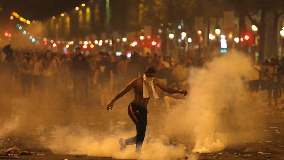 En man som sparkar på något och står bland tårgas.