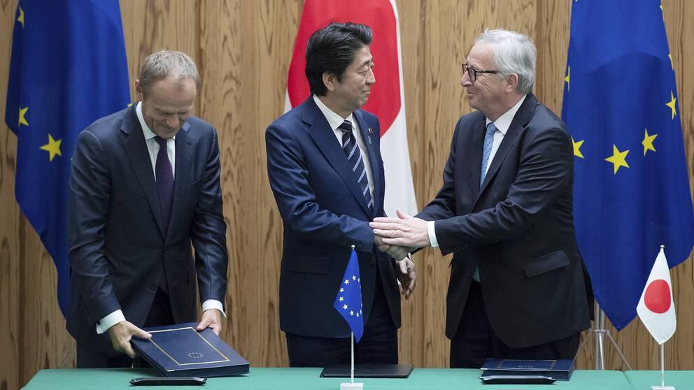 Japans premiärminister Shinzo Abe, i mitten, skakar hand med EU-kommiussionens ordförande Jean-Claude Junker efter att ha skrivit under frihandelsavtalet på tisdagen.