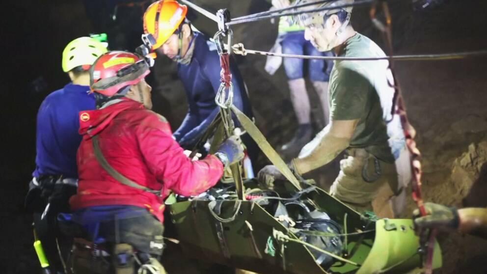 Räddningspersonal inutigrottan. På höger bild syns en av pojkarna transporteras på en bår.