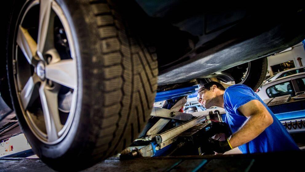 Man som reparerar en bil på en bilverkstad