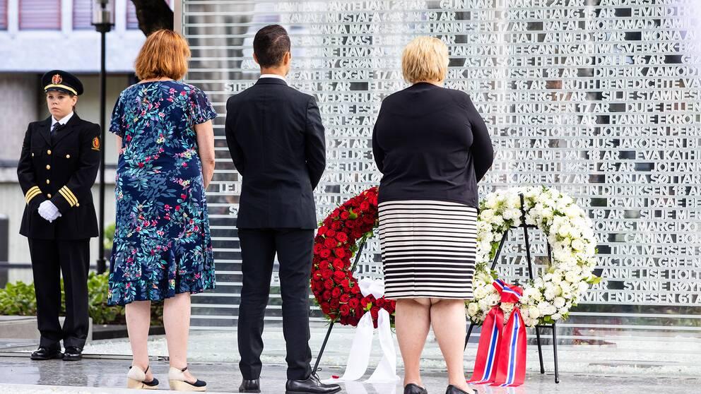 Lisbeth Røyneland, ordförande för stödgruppen för offren, AUF-ordföranden Mani Hussaini och statsminister Erna Solberg lägger kransar vid minnesmärket.