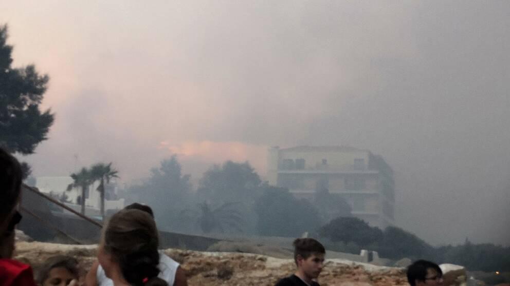 Tjock rök som nästan skymmer sikten till ett hotell från stranden