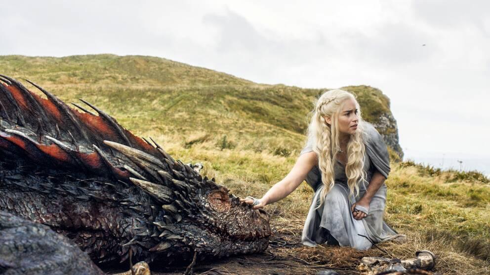 En bild från serien Game of Thrones där en av huvudpersonerna klappar en drake.