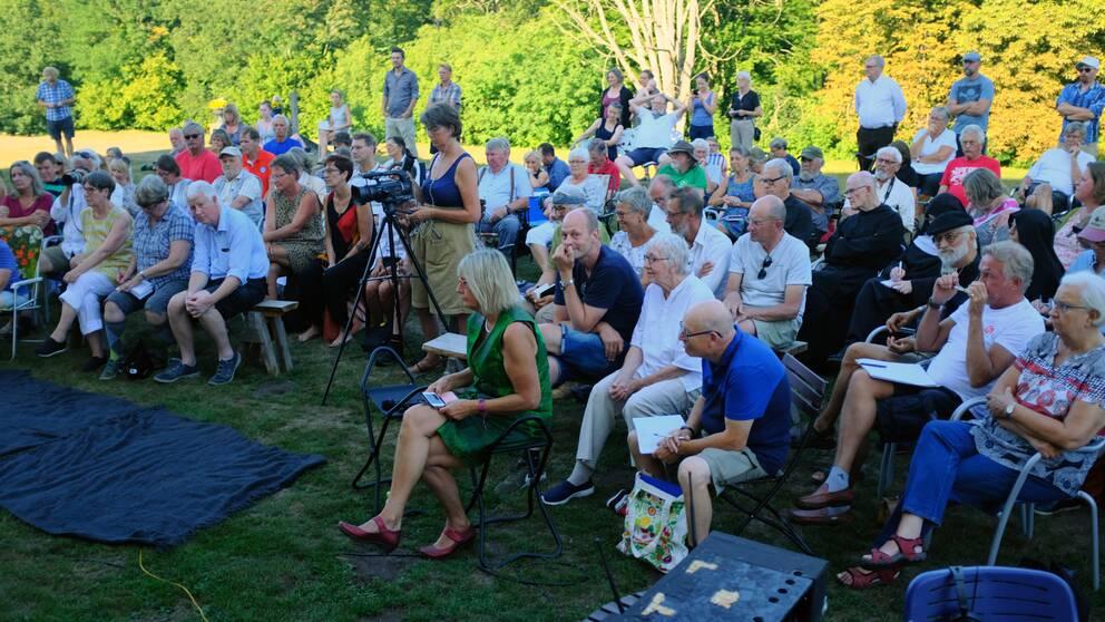Folksamling på bänkar och stolar, kvinna med kamerautrustning i mitten.