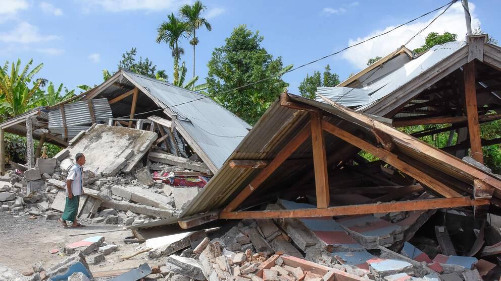 En man inspekterar skadorna på ett hus efter jordskalvet på ön Lombok.