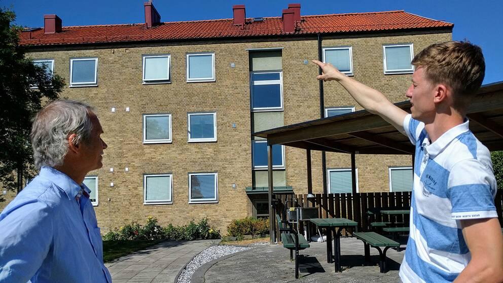 Två män framför flerfamiljshus, en pekar