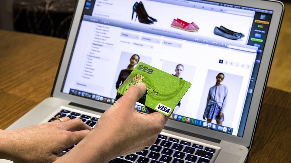 Privatperson håller sitt gröna SEB-kontokort framför datorn redo att handla på nätet.
