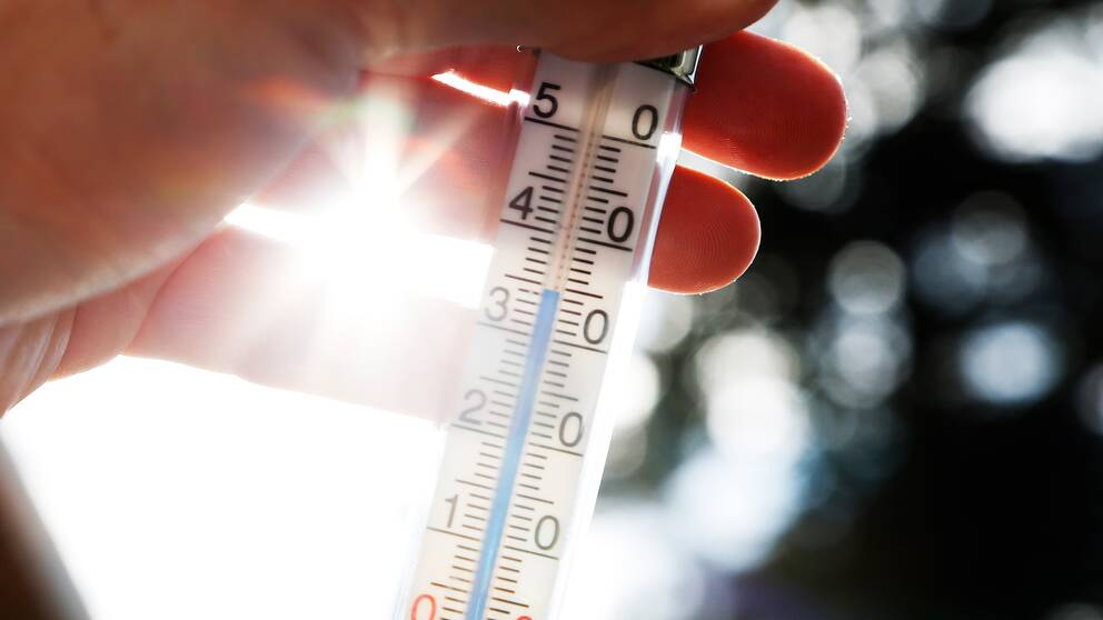 Hand som håller i termometer