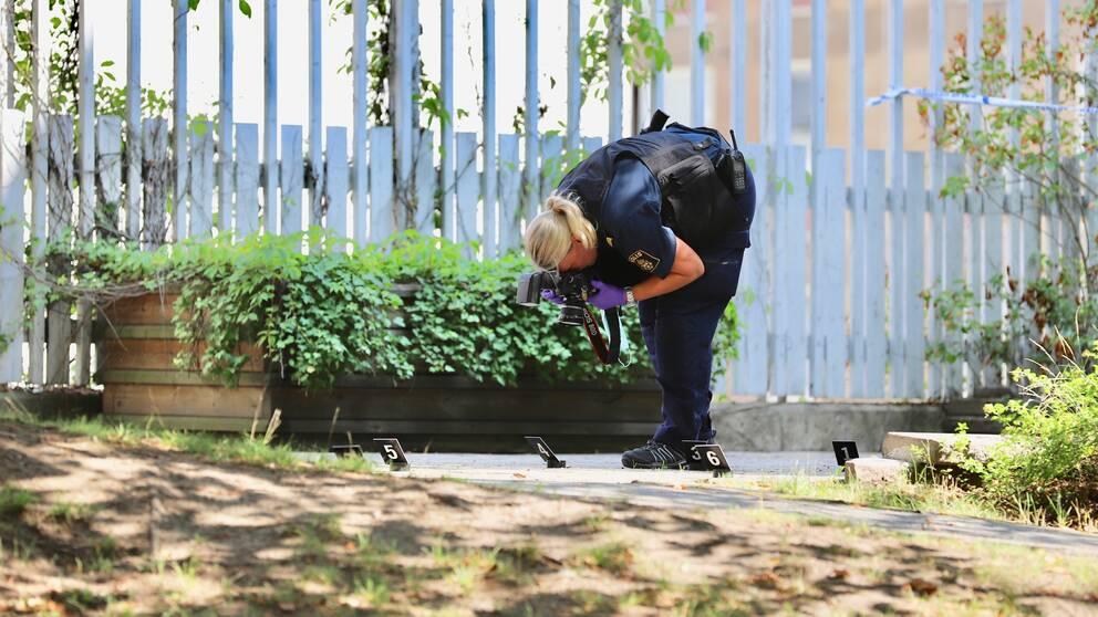 En polis som undersöker platsen där mannen sköts av polisen.