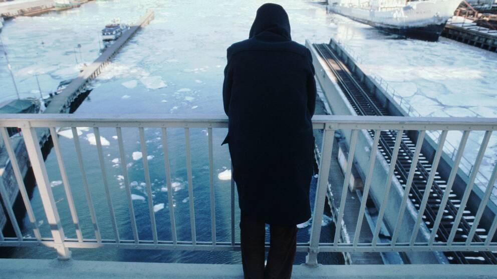 En person som inte går att identifiera står och tittar ut över en bro