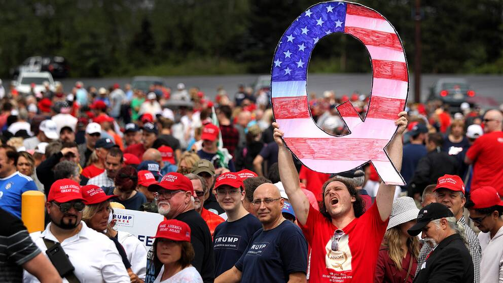 Anhängare till president Donald Trump samlade. En av dem står längst fram och håller upp ett stort Q färgad i den amerikanska flaggans färger