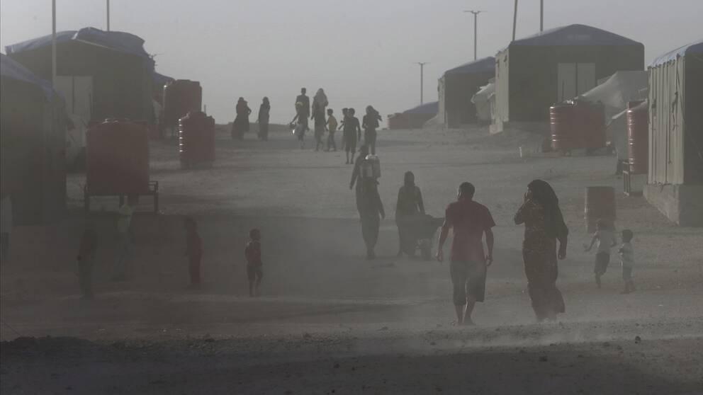 Människor går uppför en grusväg i ett flyktingläger i Syrien