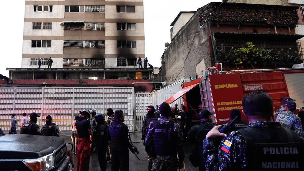 Militär och polis utanför en brandskadad byggnad i Venezuela.