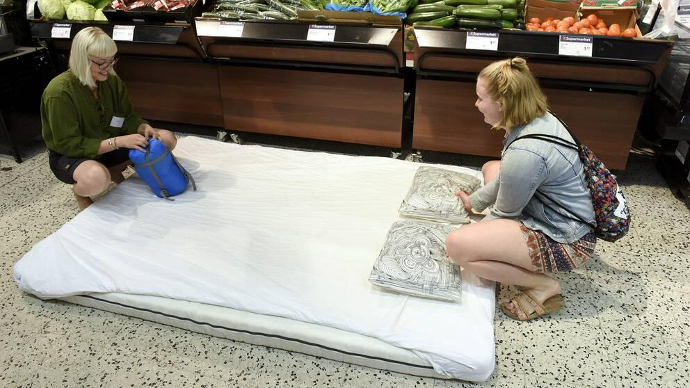 Kvinnor bäddar i matbutiken i Helsingfors där de ska sova för att undvika hettan ute.