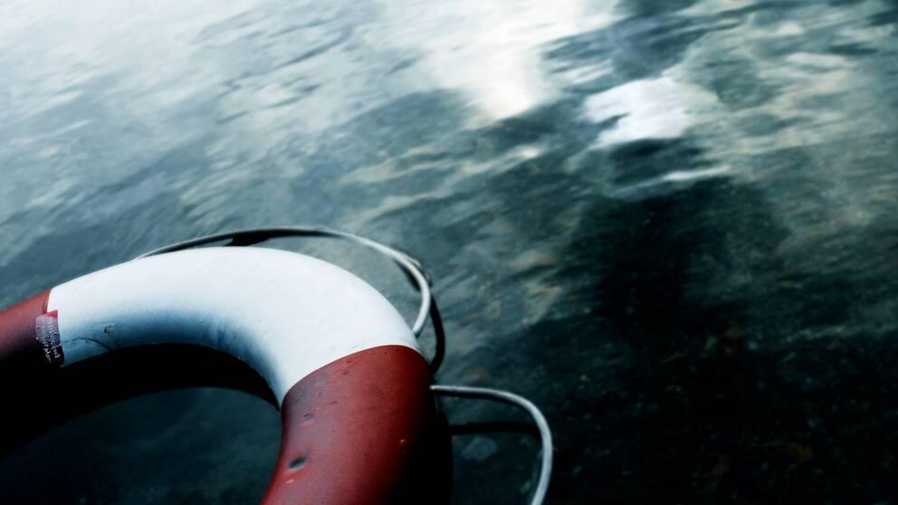 närbild livboj som flyter på vatten, mörk och dyster bild