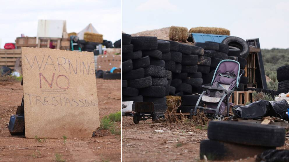 En skylt som varnar för att närma sig området. En barnvagn bland en massa bildäck på området.