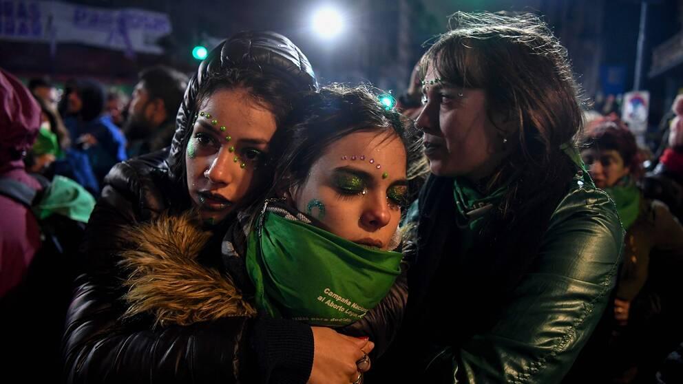Människor som vill tillåta abort fram till vecka 14 tröstar varandra utanför kongressen i Buenos Aires efter att senaten röstat nej till förslaget.