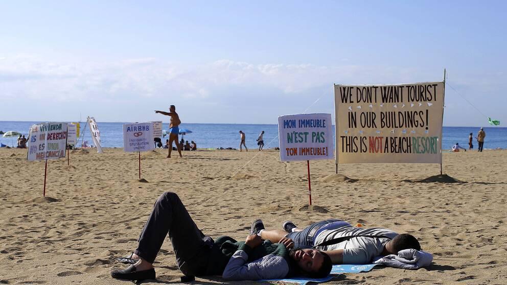 Två män ligger på en spansk sandstrand omgivna av skyltar som protesterar mot att turister bor i vanliga bostadshus.