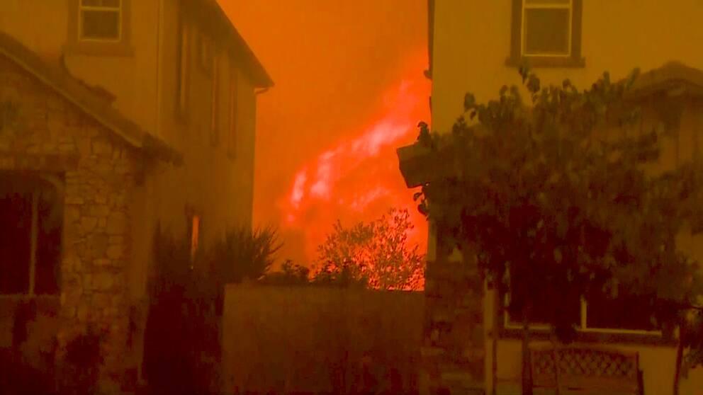Två bostadshus med stora eldsflammor mellan och bakom husen.