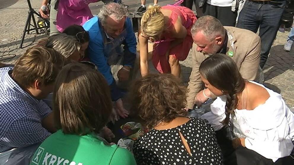 Gruppledarna för riksdagspartierna sitter på huk i ring och gör en tavla.
