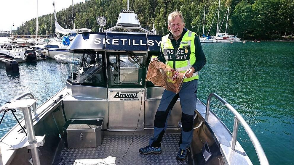 fisketillsynsman på båt i hamn