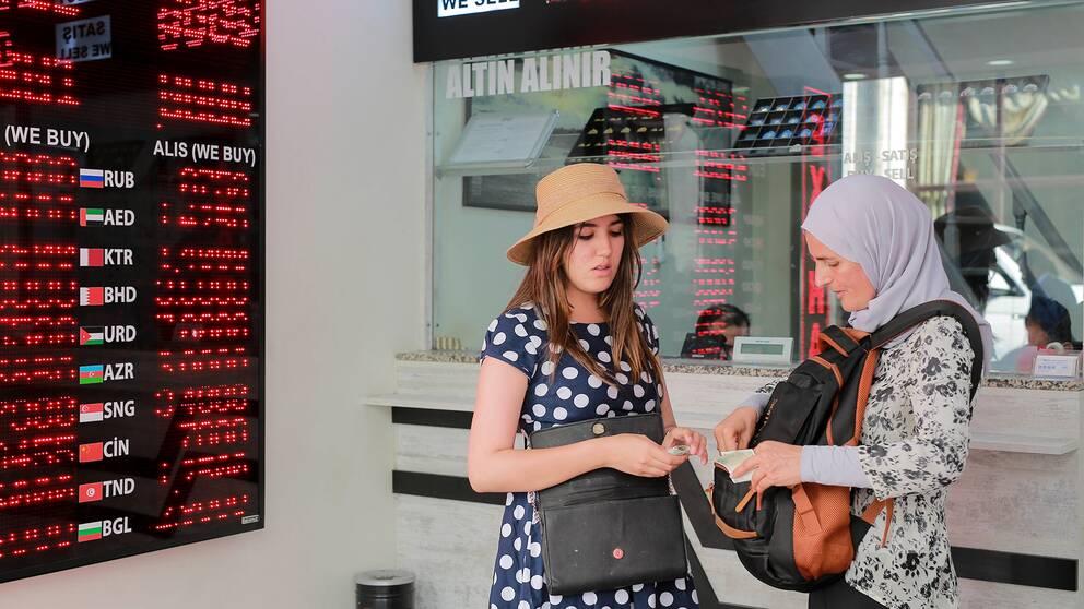 Två kvinnor växlar pengar på växlingskontor i Istanbul.