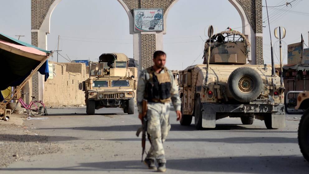 En afghansk soldat går bland stridsvagnar.