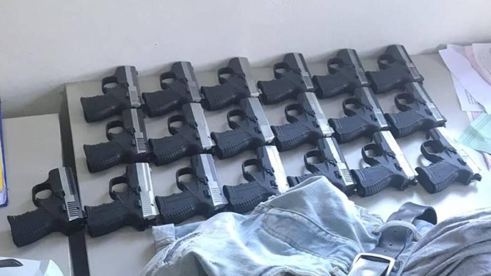 19 pistoler uppradade och ett par jeans som ligger bredvid dem.