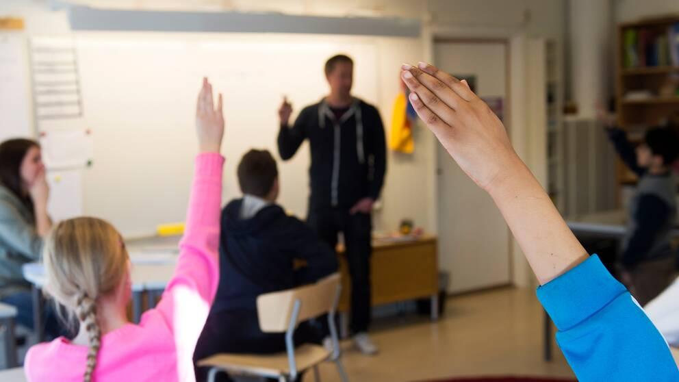 Mellanstadieelever räcker upp händerna i ett klassrum.