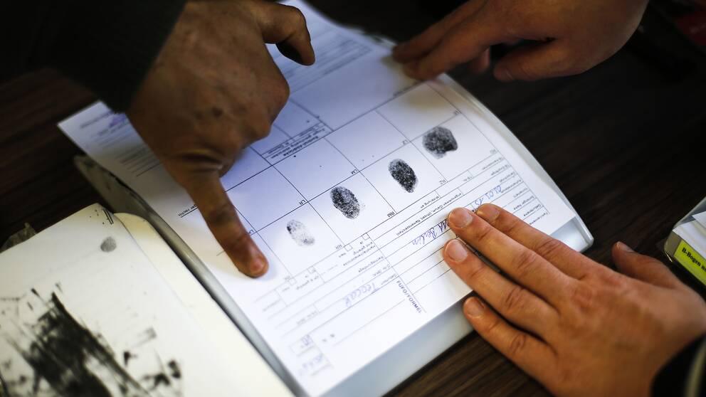 En person lämnar fingeravtryck i samband med en asylansökan