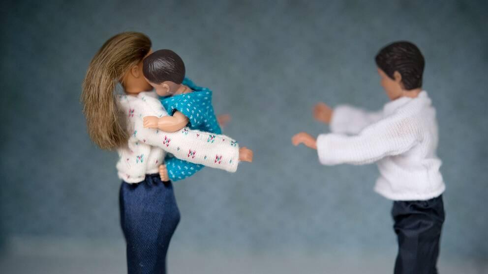 Dockor där en kvinnlig docka håller i ett barn och en manlig docka står mitt emot. Illustrerar vårdnadstvist.