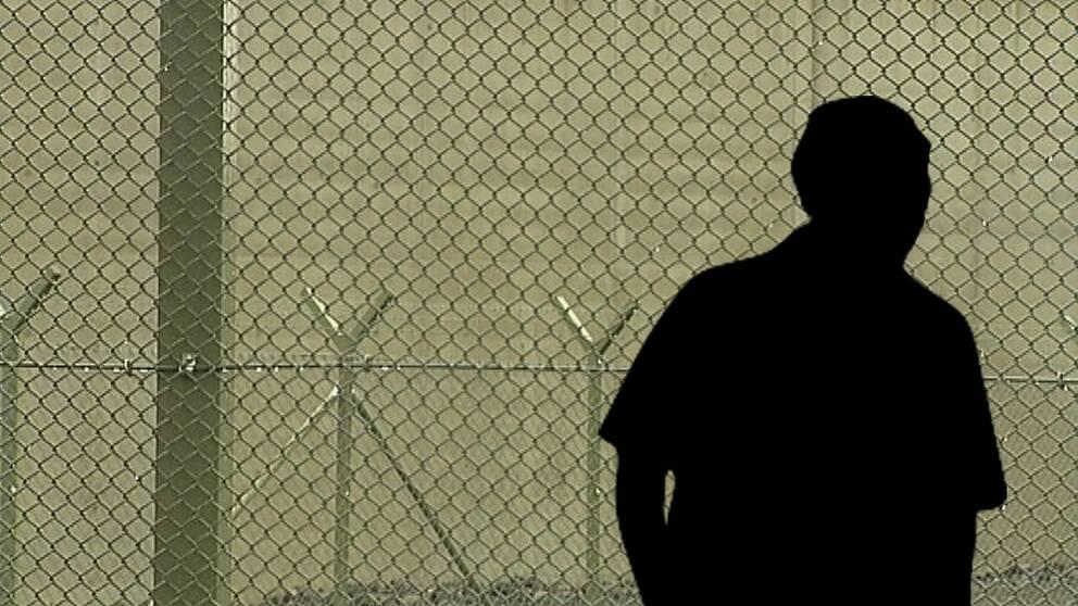 anonym silhuett av man syns mot fängelse-staket