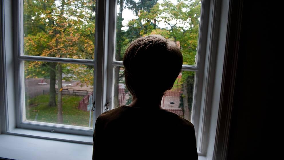 En pojke står och tittar ut genom ett fönster.