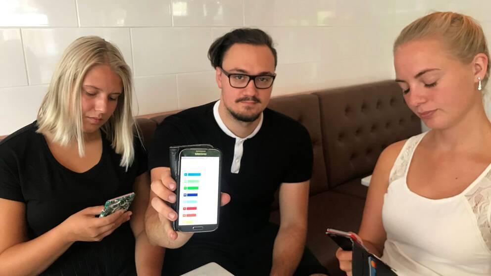 Sara, Jesper och Ebba sitter med mobilerna och gör SVT:s valkompass.