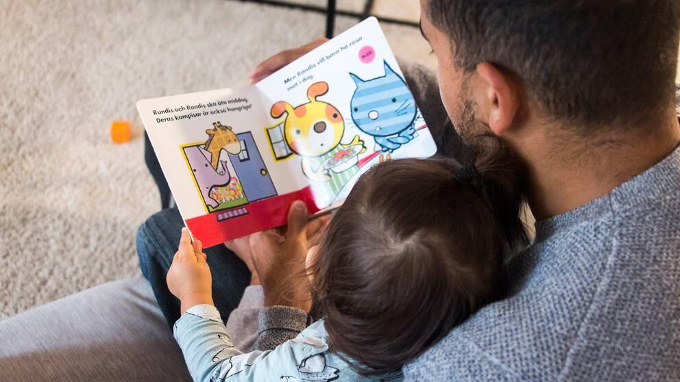 Pappa som läser i barnbok för sitt barn