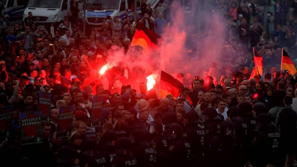 Polisen som försöker hålla tillbaka en stor grupp människor som viftar med tyska flaggor och har tänt bengaler.